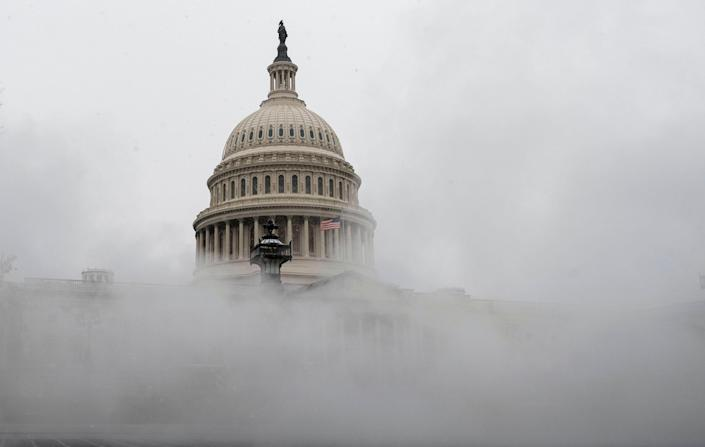 The US Capitol is enveloped with mist on Wednesday as much of the East Coast braces for snow (AFP via Getty Images)