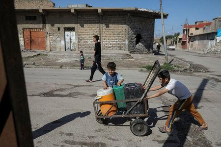 Children collect water in containers on a street in eastern Mosul