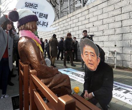 A man wearing a mask of Japanese Prime Minister Shinzo Abe kneels down in front of a statue of a girl that represents the sexual victims by the Japanese military during a rally in front of Japanese Consulate in Busan