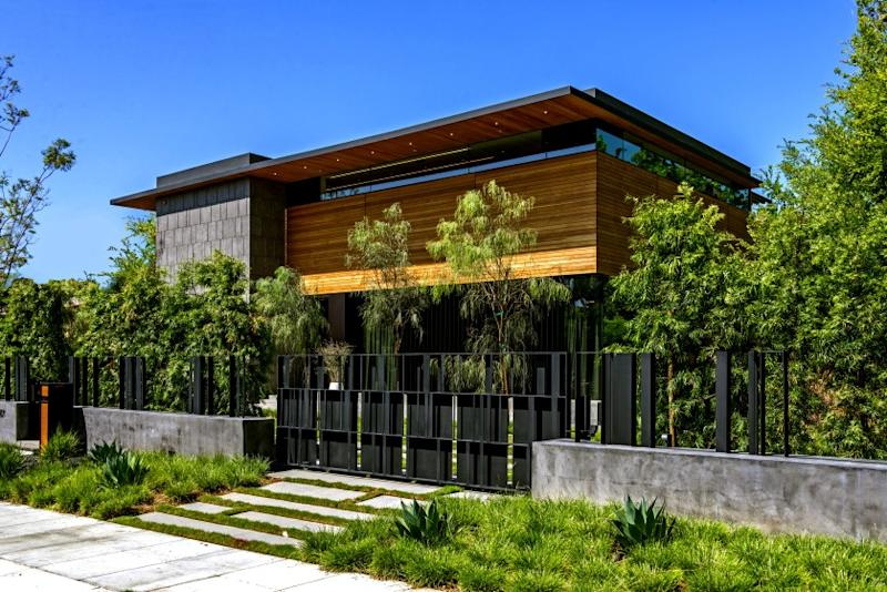 The 11,438-square-foot home, designed by Tag Front Architects, is visually striking from the street with its wood siding, stone accents and thin bands of clerestory windows. Walls of glass open the common areas to an infinity-edge swimming pool and spa. A detached guest house also lies in the backyard. Listed for $17.995 million, the modern residence has six bedrooms and 8.5 bathrooms including a master suite with an artistic fireplace feature. A floor-to-standing fireplace divides dual living rooms that make up the common area. A designer-done kitchen sits nearby.