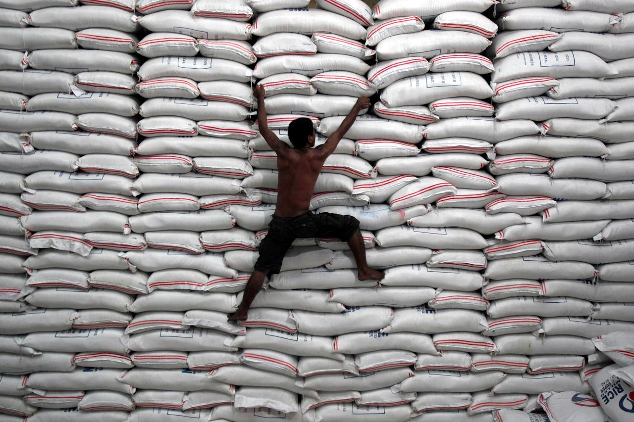 FILE PHOTO:  A worker climbs on a pile of rice stock inside a warehouse of the government National Food Authority (NFA) in Bicutan, Philippines, September 28, 2010.  REUTERS/Romeo Ranoco/File Photo