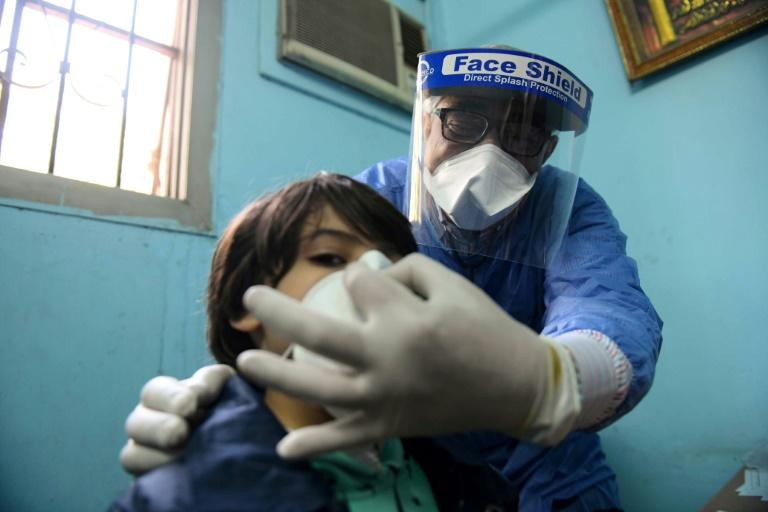 An Egyptian doctor adjusts the protective mask covering a young patient's face at the infectious diseases unit of a Cairo hospital (AFP Photo/Ahmed HASAN)