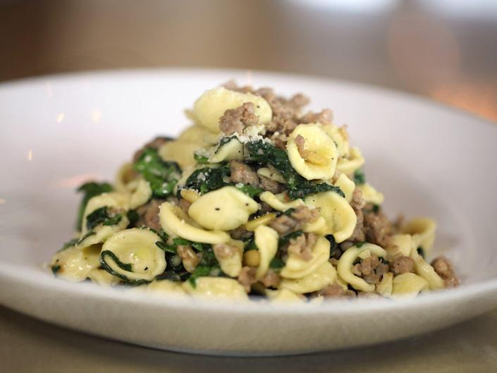 a plate of orecchiette with greens and sausage