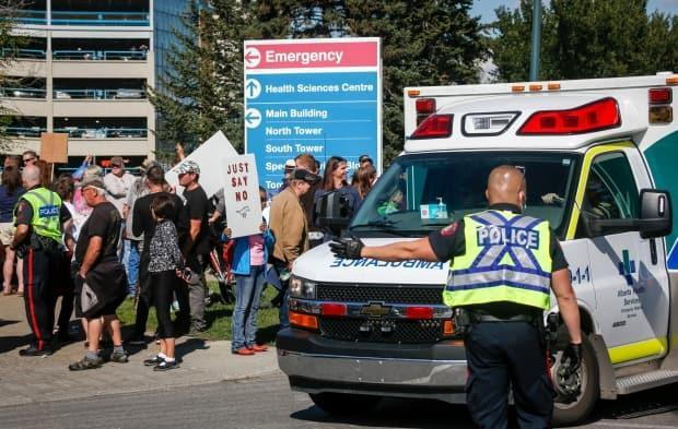 Police direct an ambulance past a protest against public health measures like COVID-19 vaccine mandates outside of Foothills hospital in Calgary on Monday, Sept. 13, 2021.  (Jeff McIntosh/Canadian Press - image credit)
