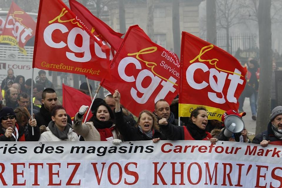 People hold up their fists and wave CGT trade union flags during a demonstration in Paris called by various French unions to protest against proposed labour reforms on March 9, 2016 (AFP Photo/Matthieu Alexandre)