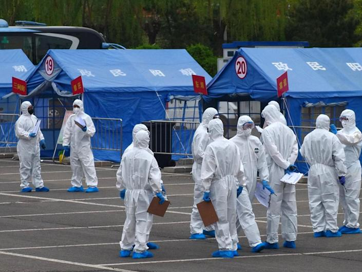 Government workers prepare to coordinate transportation of travellers from Wuhan to designated quarantine sites in Beijing on 15 April, 2020: AP