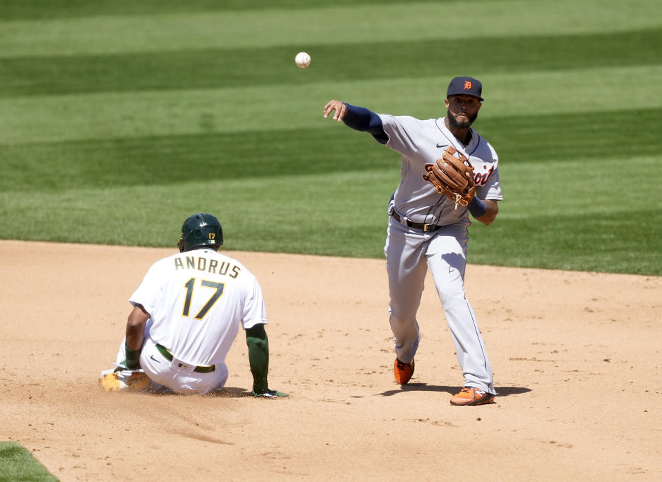 Detroit Tigers shortstop Willi Castro, right, throws to first base after forcing out Oakland Athletics' Elvis Andrus (17) at second base during the fourth inning of a baseball game on Saturday, April 17, 2021, in Oakland, Calif. (AP Photo/Tony Avelar)