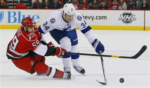 Tampa Bay Lightning's J.T. Wyman (34) and Carolina Hurricanes' Chad LaRose (59) collide during the first period of an NHL hockey game in Raleigh, N.C., Saturday, March 3, 2012. (AP Photo/Karl B DeBlaker)