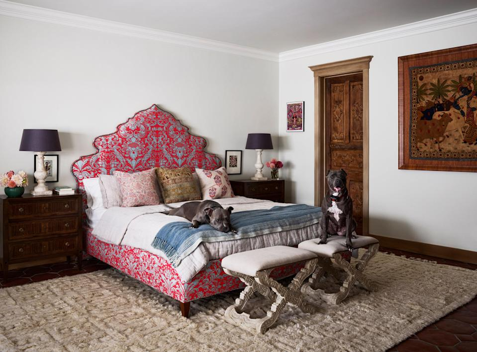 The couple's rescued pit bulls, Poe and Diamond, make themselves comfortable in the main bedroom, where the bed is upholstered in a vivid Fortuny fabric.
