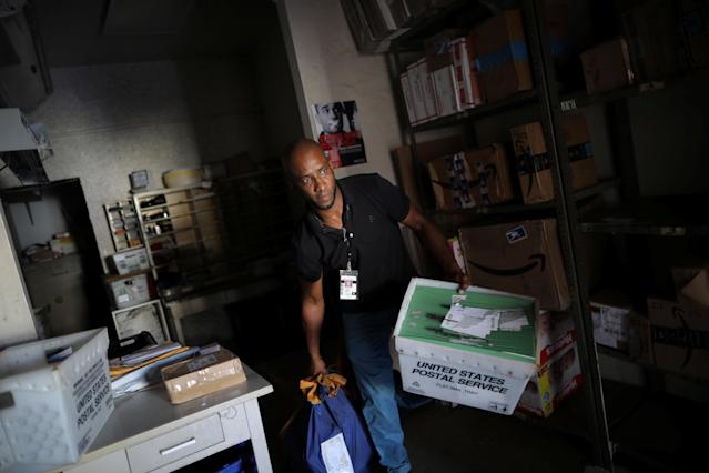 <p>Juan Rivera, from the U.S. Postal Service, picks up the mail at an area affected by Hurricane Maria in the island of Culebra, Puerto Rico, Oct. 7, 2017. (Photo: Carlos Barria/Reuters) </p>