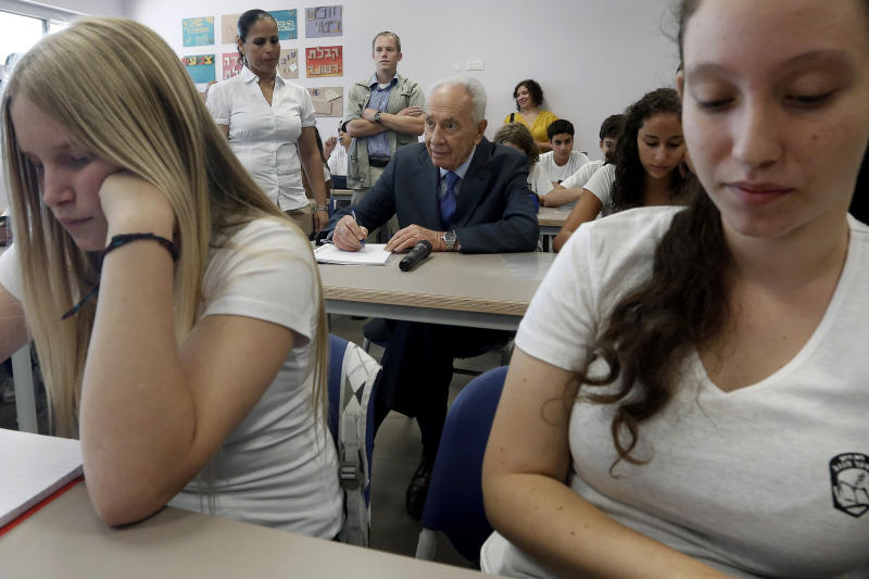 Israeli President Shimon Peres, center, sits next to students in a classroom in a new rocketproof school building, in Shaar Hanegev school, near the southern town of Sderot, Israel, Monday, Aug. 27, 2012. The 27.5 million US Dollar structure features concrete walls, reinforced windows and a unique architectural plan all designed specifically to absorb rocket fire. (AP Photo/Tsafrir Abayov)