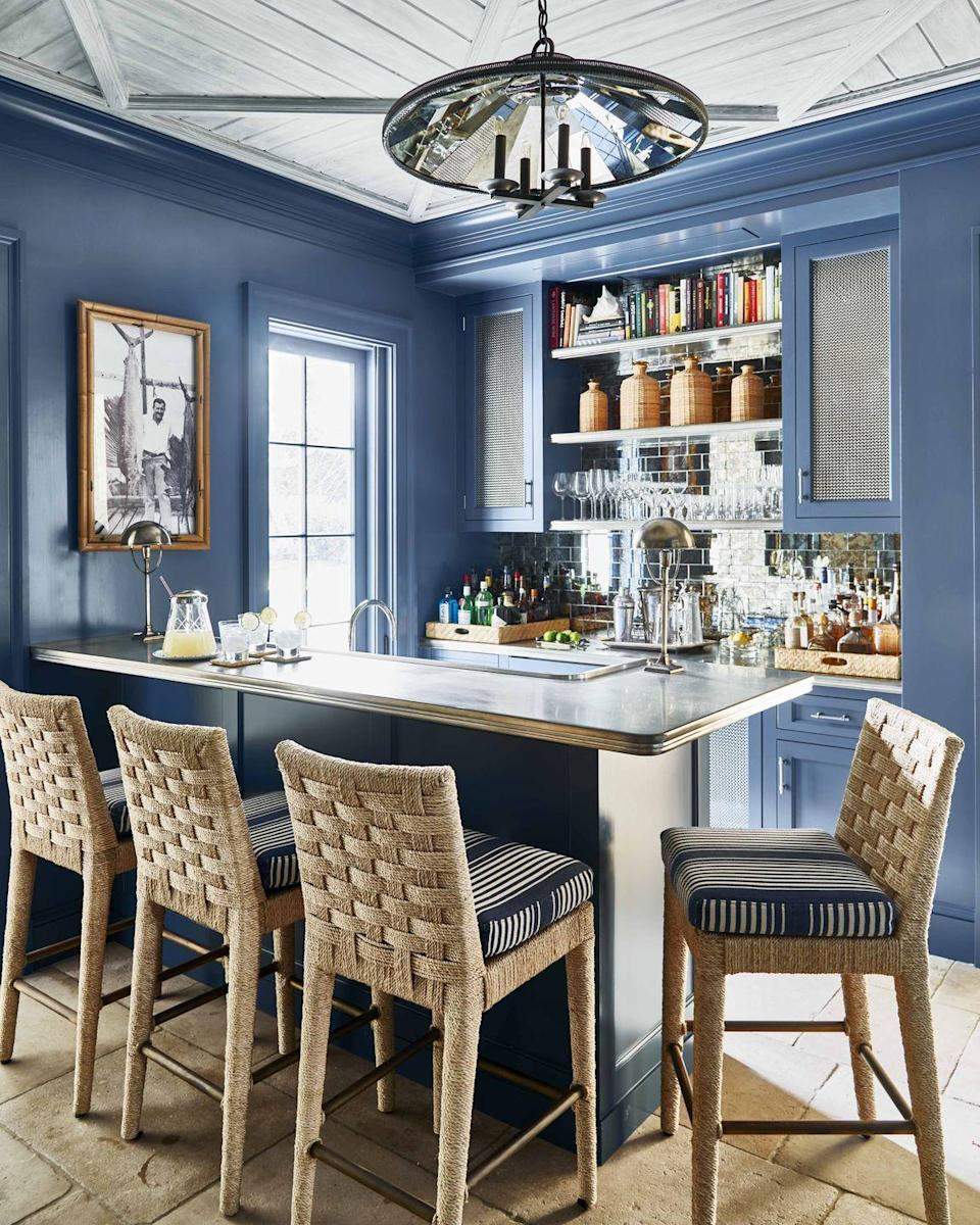 """<p>Blue walls and cabinetry, painted Van Deusen Blue by <a href=""""https://www.benjaminmoore.com/en-us"""" rel=""""nofollow noopener"""" target=""""_blank"""" data-ylk=""""slk:Benjamin Moore"""" class=""""link rapid-noclick-resp"""">Benjamin Moore</a>, along with woven barstools from <a href=""""http://www.walterswicker.com/"""" rel=""""nofollow noopener"""" target=""""_blank"""" data-ylk=""""slk:Walters Wicker"""" class=""""link rapid-noclick-resp"""">Walters Wicker</a> with cushions upholstered in a <a href=""""https://www.ralphlaurenhome.com/"""" rel=""""nofollow noopener"""" target=""""_blank"""" data-ylk=""""slk:Ralph Lauren Home"""" class=""""link rapid-noclick-resp"""">Ralph Lauren Home</a> stripe, a mirrored backsplash, and metal-trimmed counters infuse this <a href=""""https://www.veranda.com/decorating-ideas/g25422808/0064-0073-flight-of-fancy-january-2019/"""" rel=""""nofollow noopener"""" target=""""_blank"""" data-ylk=""""slk:Palm Beach home bar"""" class=""""link rapid-noclick-resp"""">Palm Beach home bar</a> designed by <a href=""""http://phoebehoward.net/"""" rel=""""nofollow noopener"""" target=""""_blank"""" data-ylk=""""slk:Phoebe Howard"""" class=""""link rapid-noclick-resp"""">Phoebe Howard</a> with a nautical vibe. </p>"""