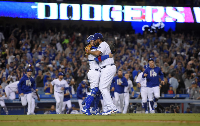 Los Angeles Dodgers relief pitcher Kenley Jansen, right, and catcher Yasmani Grandal celebrate the team's 4-2 win over the San Francisco Giants and clinch of the NL West title, after a baseball game Friday, Sept. 22, 2017, in Los Angeles. (AP Photo/Mark J. Terrill)
