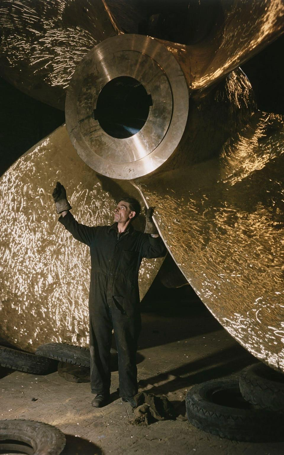 A metalworker at J Stone & Co checks the propeller for the ocean liner SS Orcades, 1947 - Westwood/Popperfoto via Getty