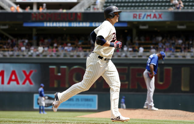 Minnesota Twins' Logan Morrison, left, jogs home after hitting a solo home run off Kansas City Royals reliever Enny Romero, right, in the sixth inning of a baseball game Wednesday, July 11, 2018, in Minneapolis. (AP Photo/Jim Mone)