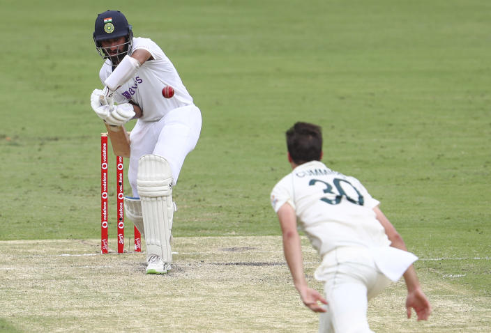 India's Cheteshwar Pujara plays at the ball bowled by Australia's Pat Cummins during play on day two of the fourth cricket test between India and Australia at the Gabba, Brisbane, Australia, Saturday, Jan. 16, 2021. (AP Photo/Tertius Pickard)
