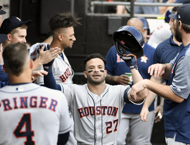 Houston Astros' Jose Altuve (27) is greeted by teammates after hitting a home run against the Chicago White Sox during the third inning of game one of a baseball doubleheader, Tuesday, Aug. 13, 2019, in Chicago. (AP Photo/David Banks)