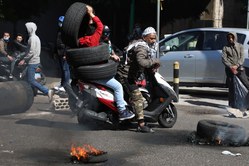 Demonstrators attempt to block a road with tires, during a protest in Beirut