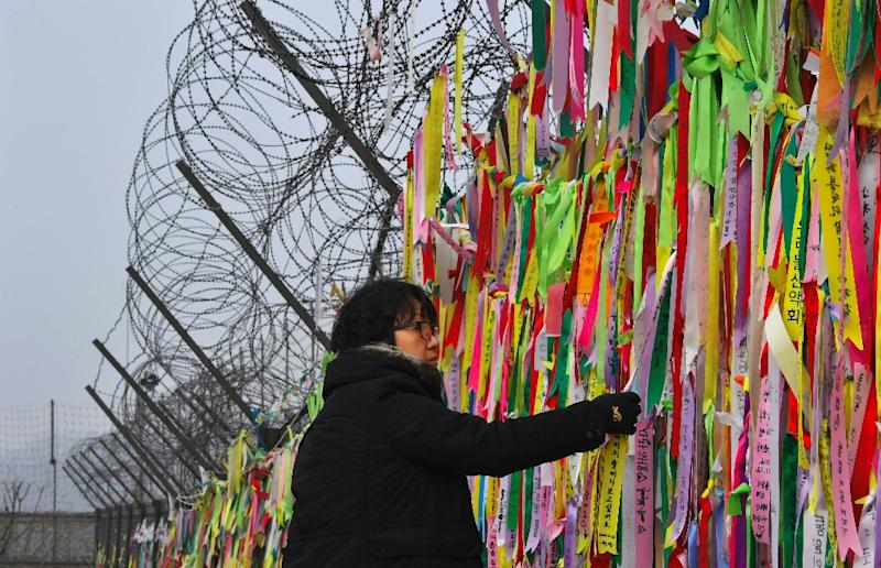A woman looks at ribbons calling for peace and reunification on a fence near the Demilitarized Zone dividing North and South Korea on January 1, 2017 (AFP Photo/JUNG Yeon-Je)