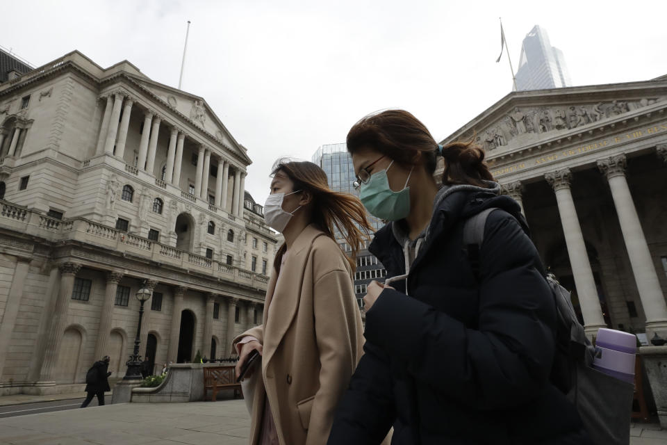 Pedestrians wearing face masks walk past the Bank of England in London, Wednesday, March 11, 2020. Britain's Chancellor of the Exchequer Rishi Sunak will announce the first budget since Britain left the European Union. (AP Photo/Matt Dunham)