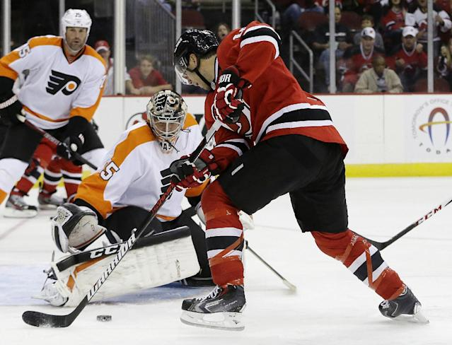 New Jersey Devils right wing Steve Bernier, right, scores on a shot as Philadelphia Flyers goalie Steve Mason defends his goal during the second period of an NHL preseason hockey game, Thursday, Sept. 26, 2013, in Newark, N.J. (AP Photo/Julio Cortez)