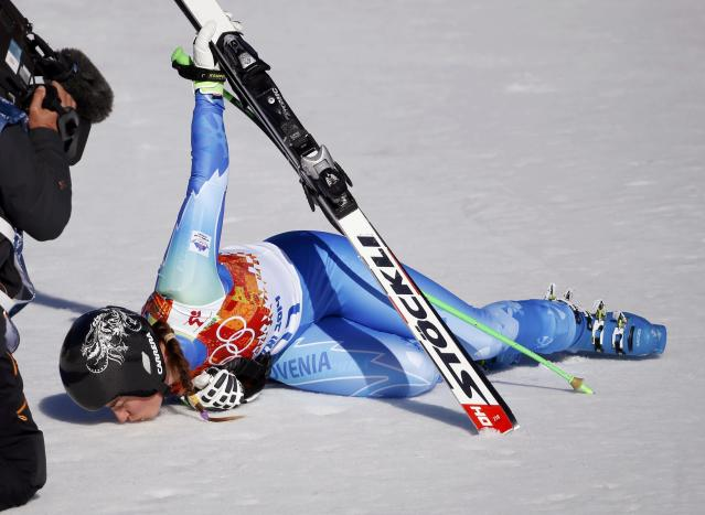 Slovenia's Tina Maze kisses the ground after winning the women's alpine skiing downhill race at the 2014 Sochi Winter Olympics February 12, 2014. REUTERS/Leonhard Foeger (RUSSIA - Tags: OLYMPICS SPORT SKIING TPX IMAGES OF THE DAY)