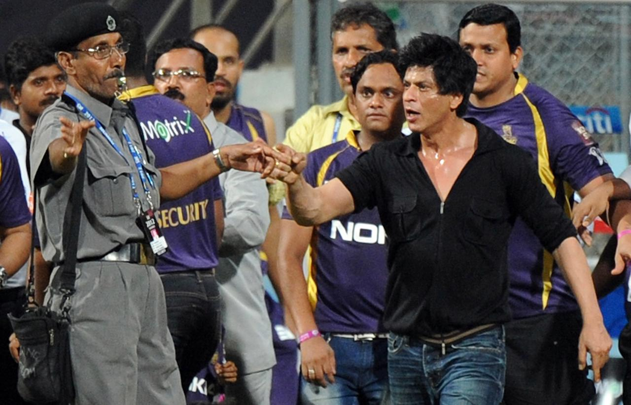 Bollywood actor and Indian Premier League franchise Kolkata Knight Riders co-owner Shah Rukh Khan (R) gestures towards a security guard blowing a whistle to direct children accompanying him off the playing field after the IPL Twenty20 cricket match between Mumbai Indians and Kolkata Knight Riders at The Wankhede Stadium in Mumbai early morning on May 17, 2012.  Khan is to be banned by Mumbai Cricket Association from entering the Wankhede Stadium for life following an altercation he had with security and officials of the association. RESTRICTED TO EDITORIAL USE. MOBILE USE WITHIN NEWS PACKAGE    AFP PHOTO/Indranil MUKHERJEE