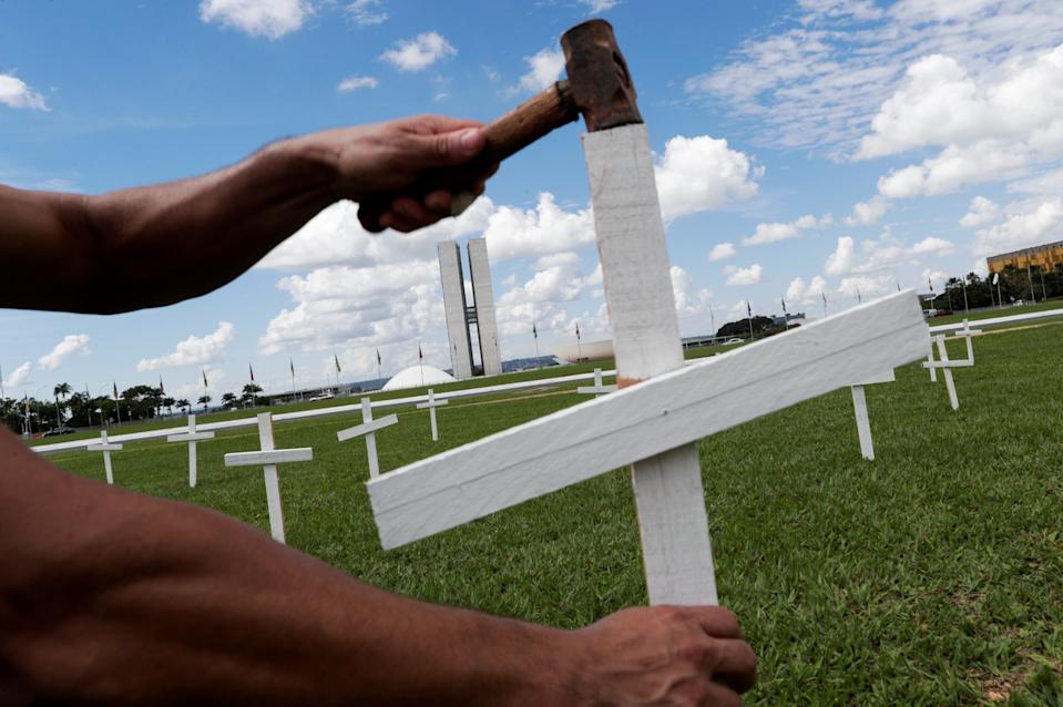 A demonstrator places a cross symbolising the ones who died from the coronavirus disease (COVID-19) in front of the National Congress in Brasilia, Brazil April 27, 2021. REUTERS/Ueslei Marcelino     TPX IMAGES OF THE DAY