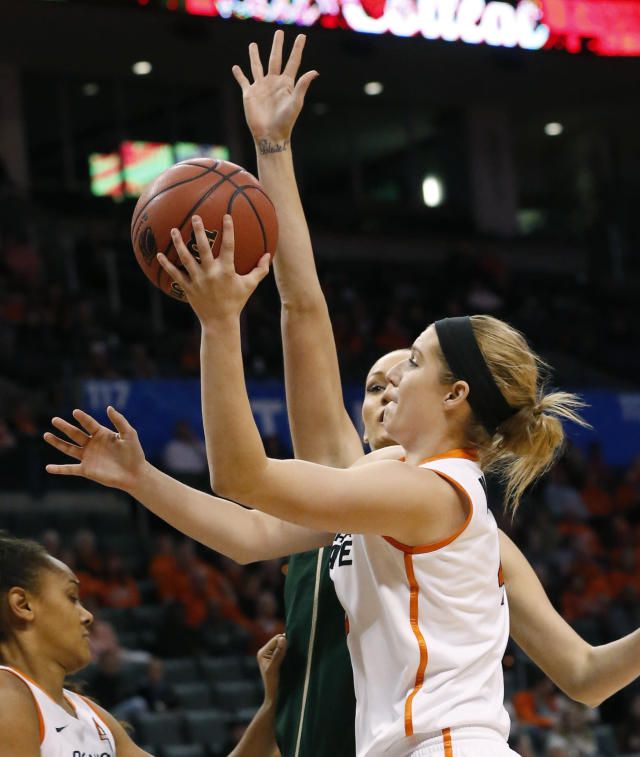 Oklahoma State forward Liz Donohoe (4) shoots in front of South Florida guard Inga Orekhova (13) in the first half of an NCAA college basketball game at the All College Classic in Oklahoma City, Saturday, Dec. 14, 2013. (AP Photo/Sue Ogrocki)