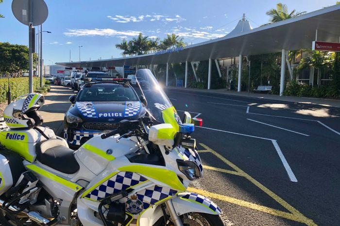 A police motorbike and cars line the street outside the Sunshine Coast Airport on 6 June, 2020.