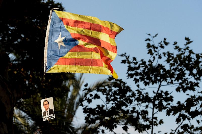 "An ""Estelada"" with a picture of Catalonia's regional government president and leader of the Catalan Democratic Convergence party Artur Mas reading ""Artur Mas imputed by 9n"" is waved as he arrives at the TSJC on October 15, 2015 in Barcelona (AFP Photo/Josep Lago)"