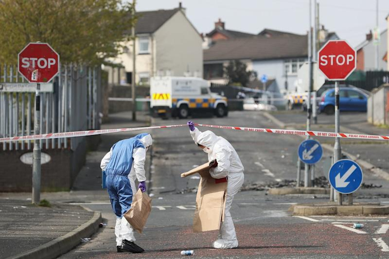 Forensic officers at the scene of the killing in Londonderry on Friday (PA)
