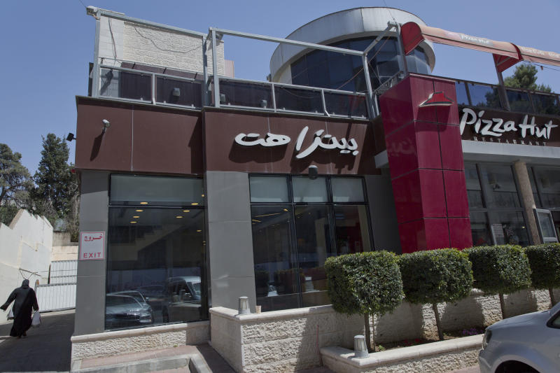 A woman walks by a Palestinian branch of the Pizza Hut company, in the West Bank city of Ramallah, Wednesday, May 10, 2017. Pizza Hut has issued an apology for an Israeli Facebook ad that mocked the leader of a mass Palestinian hunger strike posted after video emerged claiming to show him secretly snacking. It showed a Pizza box in a prison cell with text asking if Marwan Barghouti would have rather broken his fast with Pizza. Israel's Prison Service earlier released footage it says shows Barghouti eating what it said were cookies and a candy bar. The claim was dismissed by Palestinians as an attempt to undermine the strike, now in its 24th day. (AP Photo/Nasser Nasser)