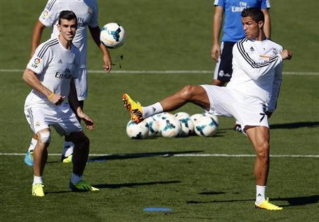 Real Madrid's Bale and Ronaldo challenge for the ball during their training session at Valdebebas sports grounds in Madrid