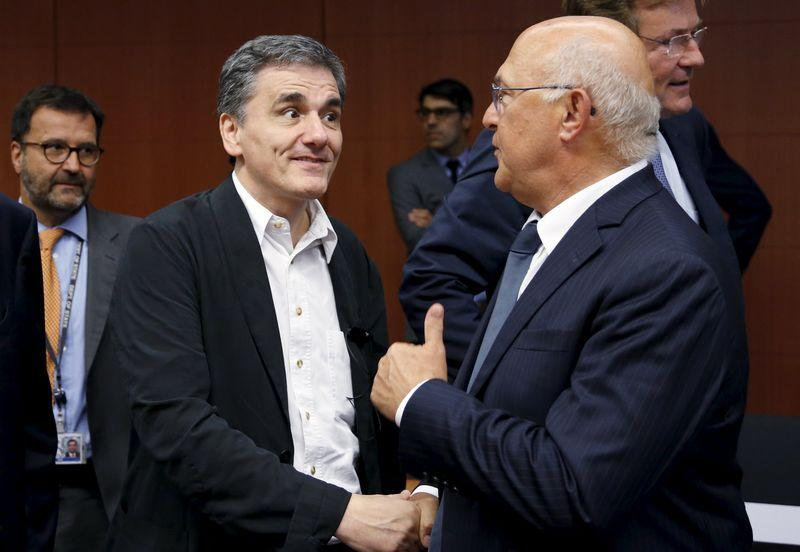 Greek Finance Minister Tsakalotos listens to his French counterpart Sapin during a euro zone finance ministers meeting in Brussels