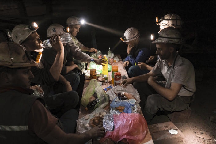 Bosnian coal miners break fast in the underground at a mine in Zenica, Bosnia, Thursday, April 29, 2021. Inside mine shafts, one can't see sunset, but miners consult their watches and smartphones for the right time to sit down, unwrap their food and break their daily fast together. (AP Photo/Kemal Softic)
