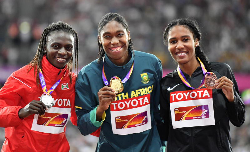 FILE - In a Sunday, Aug. 13, 2017 file photo, Women's 800 meters gold medalist South Africa's Caster Semenya, center, stands with silver medalist Burundi's Francine Niyonsaba, left, and bronze medalist United States' Ajee Wilson, right, on the podium at the World Athletics Championships in London. Defending 800-meter champion Caster Semenya won't stand on the podium with a medal draped around her neck at the World Championships in Doha, Qatar. On the 10th anniversary of Semenya blowing away the field in the 800 at the 2009 World Championships in Berlin, she won't comply with the International Association of Athletics Federations' latest version of a regulation to lower her level of natural testosterone. (AP Photo/Martin Meissner, File)