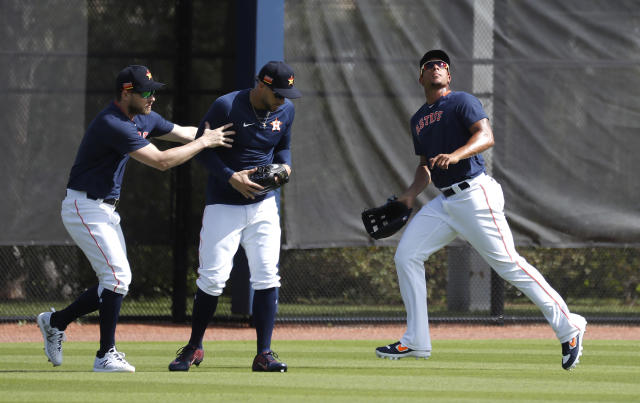 Houston Astros outfielders Josh Reddick and George Springer duck for cover as Michael Brantley runs after a fly ball during spring training baseball practice, Tuesday, Feb. 18, 2020 in West Palm Beach, Fla. (Karen Warren/Houston Chronicle via AP)