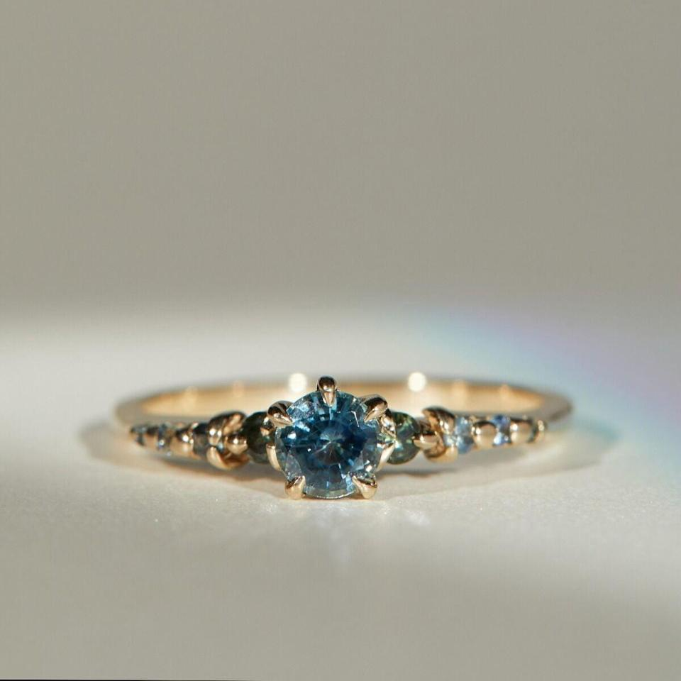 """<p>The beautiful blue and green sapphire stones that lie atop the <a href=""""https://www.popsugar.com/buy/Sapphire-Cyndra-Ring-530018?p_name=Sapphire%20Cyndra%20Ring&retailer=catbirdnyc.com&pid=530018&price=1%2C325&evar1=fab%3Aus&evar9=7954958&evar98=https%3A%2F%2Fwww.popsugar.com%2Fphoto-gallery%2F7954958%2Fimage%2F47020643%2FSapphire-Cyndra-Ring&list1=shopping%2Cwedding%2Cjewelry%2Crings%2Cbride%2Cengagement%20rings%2Cfashion%20shopping&prop13=api&pdata=1"""" rel=""""nofollow noopener"""" class=""""link rapid-noclick-resp"""" target=""""_blank"""" data-ylk=""""slk:Sapphire Cyndra Ring"""">Sapphire Cyndra Ring</a> ($1,325) look so pretty.</p>"""