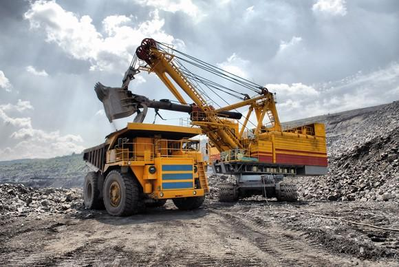 An excavator loading a dump truck in an open-pit gold mine.