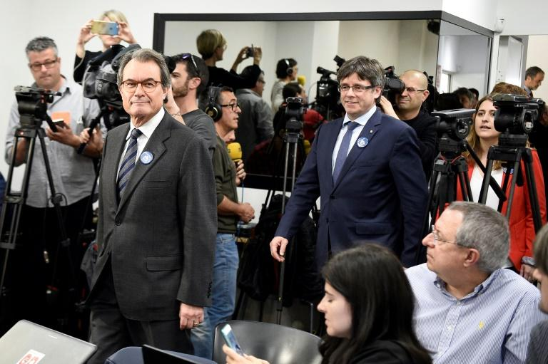 Former President of the Catalan Government and leader of Partit Democrata Europeu Catala Catalan European Democratic Party Artur Mas (L) followed by President of the Catalan Government Carles Puigdemont in Barcelona on March 13, 2017