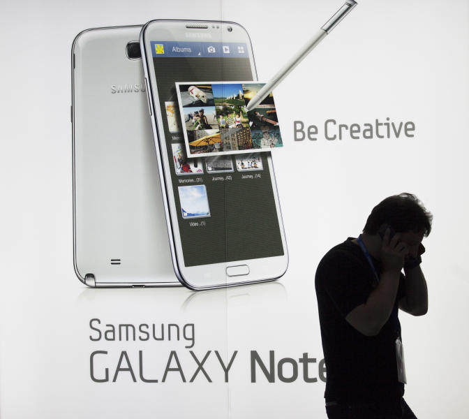 A man uses a cell phone as he stands in front of a display of the new Samsung Galaxy Note II smart phone during a media preview at the Samsung stand at the IFA consumer electric fair in Berlin, Thursday, Aug. 30, 2012. (AP Photo/Markus Schreiber)