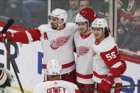 Detroit Red Wings' Filip Zadina, center, of Czech Republic is congratulated by teammates on his first of two goals off Minnesota Wild's Devan Dubnyk in the first period of an NHL hockey game Wednesday, Jan. 22, 2020, in St. Paul, Minn. (AP Photo/Jim Mone)