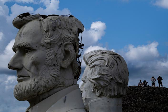 Busts of former US Presidents Abraham Lincoln and Andrew Jackson(R) can be seen as people get an overview from a mountain of mulch while they tour the decaying remains of salvaged busts of former US Presidents August 25, 2019, in Williamsburg, Virginia. (Photo: Brendan Smialowski/AFP/Getty Images)