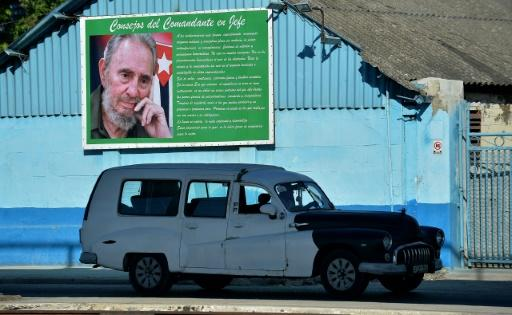 An old American car drives next to a poster of Cuban late leader Fidel Castro Havana in November 2019