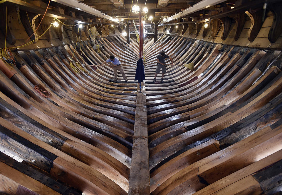 FILE- In this Nov. 3, 2017 file photo, shipwrights Jamie Kirschner, left, and Tucker Yaro, clean out the hold of the Mayflower II at Mystic Seaport in Mystic, Conn. After undergoing more than three years of major renovations in Connecticut and months of delays due to the COVID-19 pandemic, the replica of the Mayflower is ready to return home. (Sean D. Elliot/The Day via AP, File)