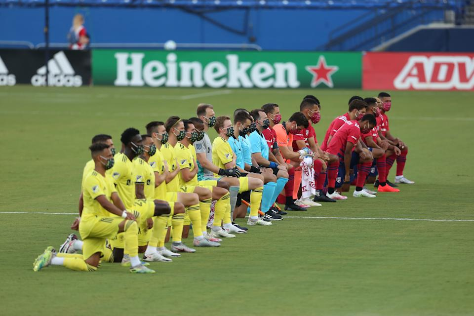 Officials and players from FC Dallas (right) and Nashville SC took a knee to protest police brutality and systemic racism during the national anthem prior to Wednesday's MLS game game between the teams. (Omar Vega/Getty Images)
