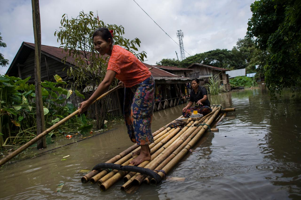 <p>A woman steers a bamboo-raft along a flooded road in Taungnu township of Bago region in Myanmar on Aug. 31, 2018. (Photo: Ye Aung Thu/AFP/Getty Images) </p>