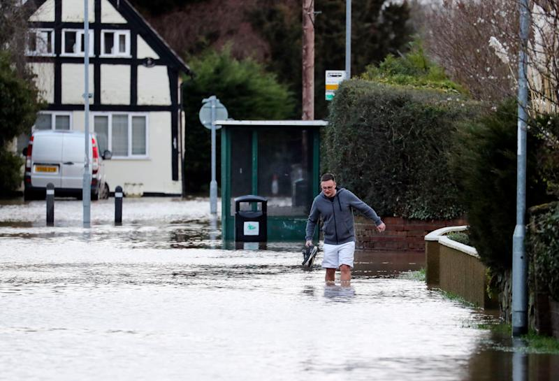 A man wades through flood water in Hereford. (Photo: PA)