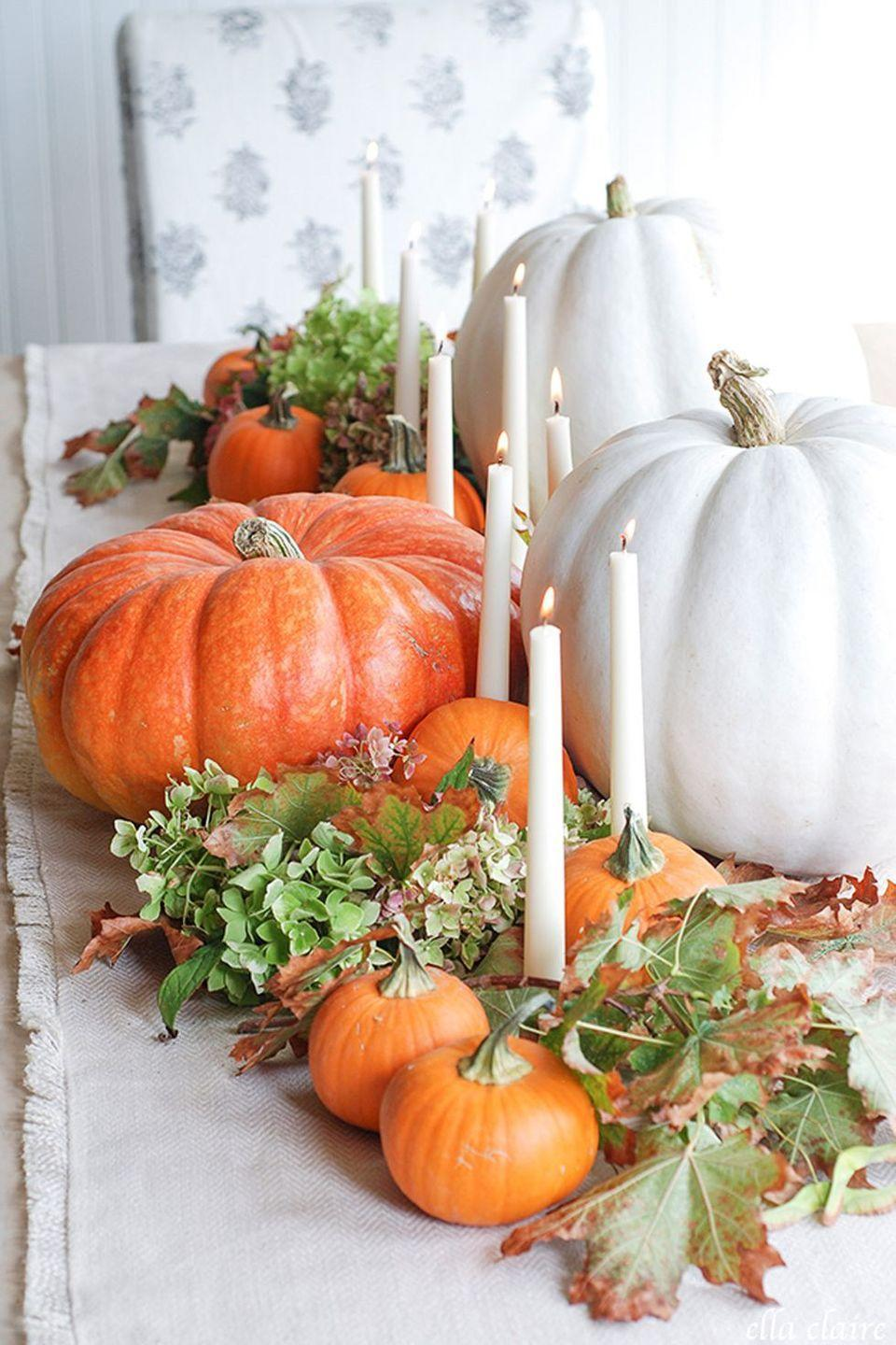 """<p>Can't decide on a color scheme? Give yourself the best of both worlds with this neat centerpiece idea, which brings together a neutral runner, white taper candles, and a dash of bold color.</p><p><strong>Get the tutorial at <a href=""""http://www.ellaclaireinspired.com/fall-2015-home-tour/"""" rel=""""nofollow noopener"""" target=""""_blank"""" data-ylk=""""slk:Ella Claire"""" class=""""link rapid-noclick-resp"""">Ella Claire</a>.</strong></p><p><strong><a class=""""link rapid-noclick-resp"""" href=""""https://www.amazon.com/Factory-Direct-Craft-Artificial-Decorating/dp/B075WXYV5K?tag=syn-yahoo-20&ascsubtag=%5Bartid%7C10050.g.2130%5Bsrc%7Cyahoo-us"""" rel=""""nofollow noopener"""" target=""""_blank"""" data-ylk=""""slk:SHOP FAUX PUMPKINS"""">SHOP FAUX PUMPKINS</a><br></strong></p>"""